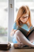Image displays a child sitting cross legged on a table reading a book.